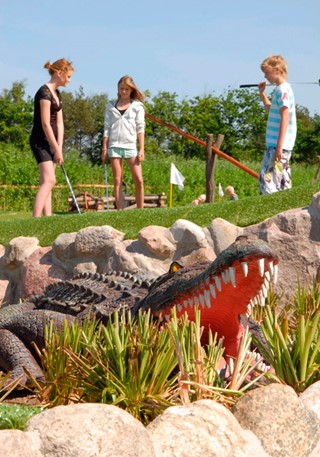 Crocodile in front of kids playing golf